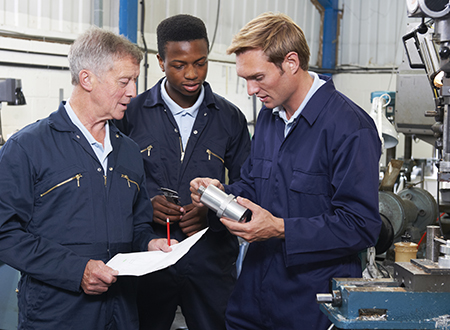 three men in blue engineering suits reviewing a steel product